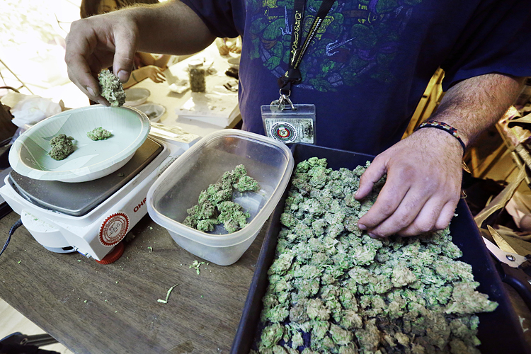 "An employee weighs portions of retail marijuana to be packaged and sold at 3D Cannabis Center in Denver, Tuesday Dec. 31, 2013. Colorado is making final preparations for marijuana sales to begin Jan. 1, a day some are calling ""Green Wednesday."" (AP Photo/Brennan Linsley)"
