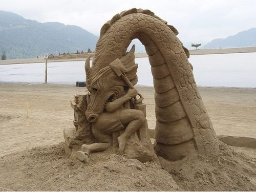 awesome pics - amazing sand sculpture of a dragon eating a man